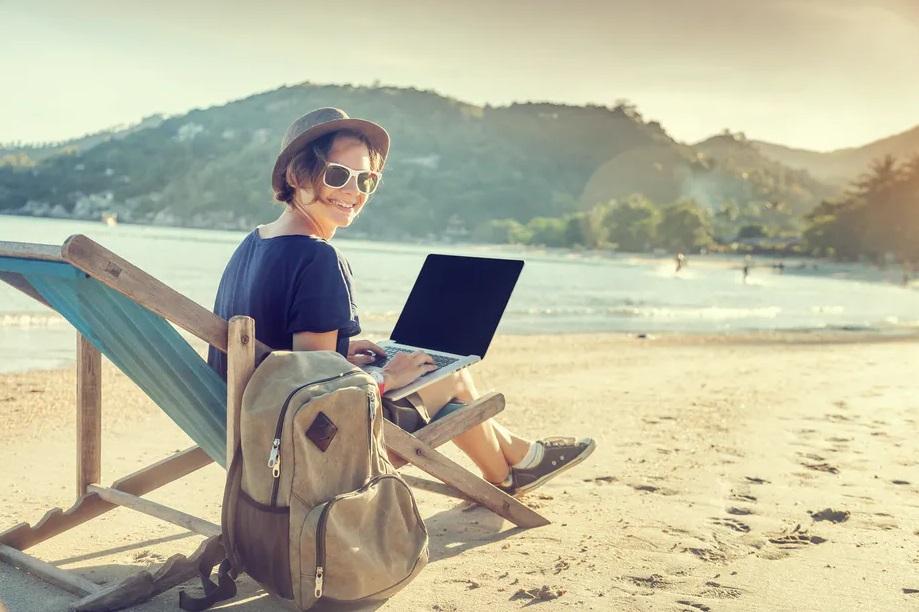 Femme à la plage avec son ordinateur