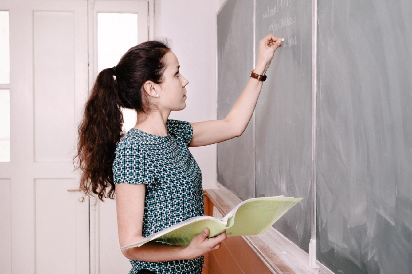 Etudiante qui écrit au tableau